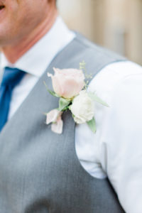 A blush and white groom's boutonnière pinned to his chest