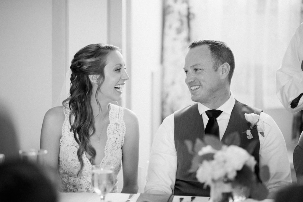 Bride and Groom laughing during speeches at their felt mansion wedding