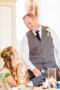 Groom smiling down at his bride during his speech at their Holland, Michigan wedding