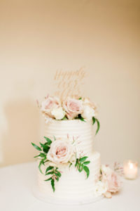 A white cake with dusty pink flowers and a gold Mr. & Mrs. topper