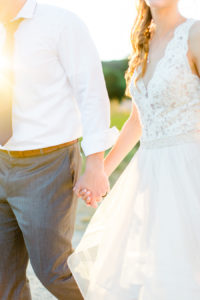 Bride and groom holding hands during sunset at their felt mansion wedding