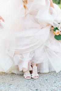 Bride showing off her shoes during sunset at her felt mansion wedding