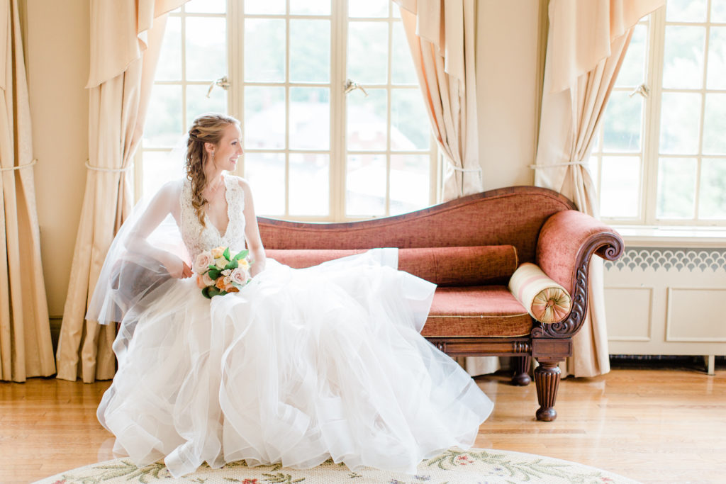 Bride smiling on a sofa in the bridal suite at her felt mansion wedding