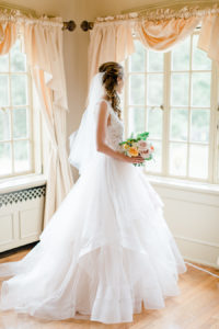 Bride looking out the window before her felt mansion wedding