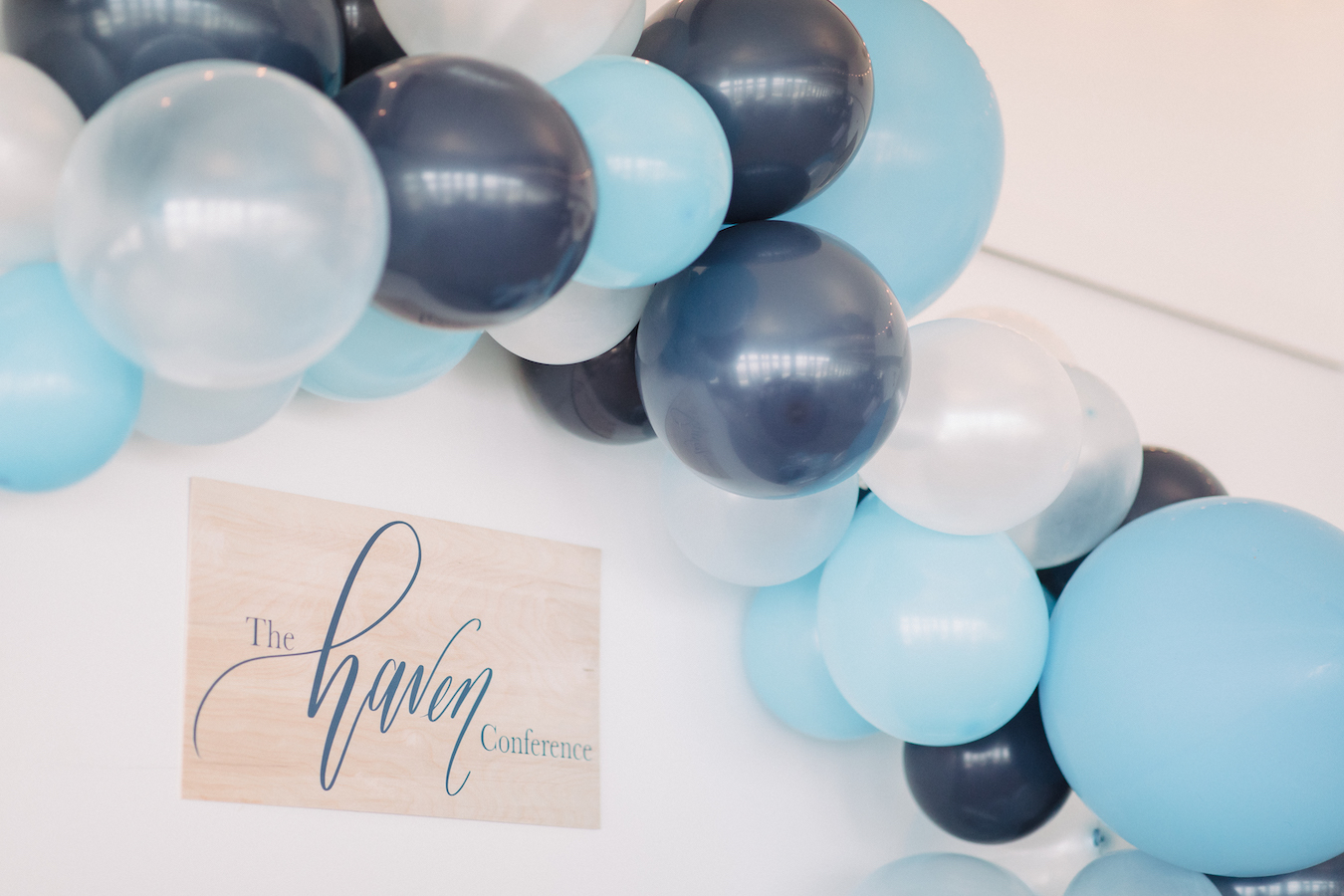Blue balloon arch with The Haven Conference logo