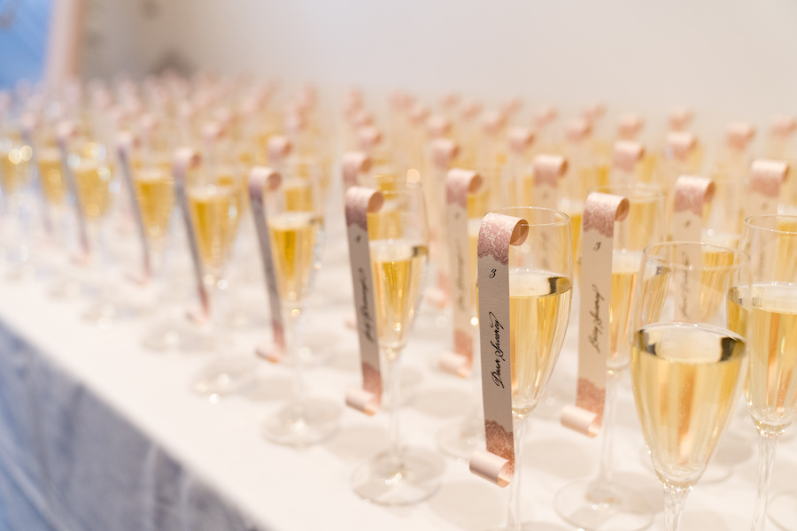 Champagne escort cards lined on a table during a Loft 310 wedding
