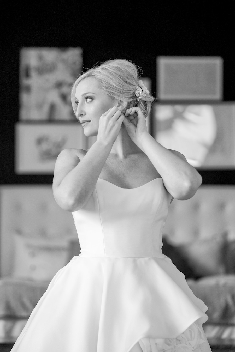 A bride putting on her earrings the morning of her wedding