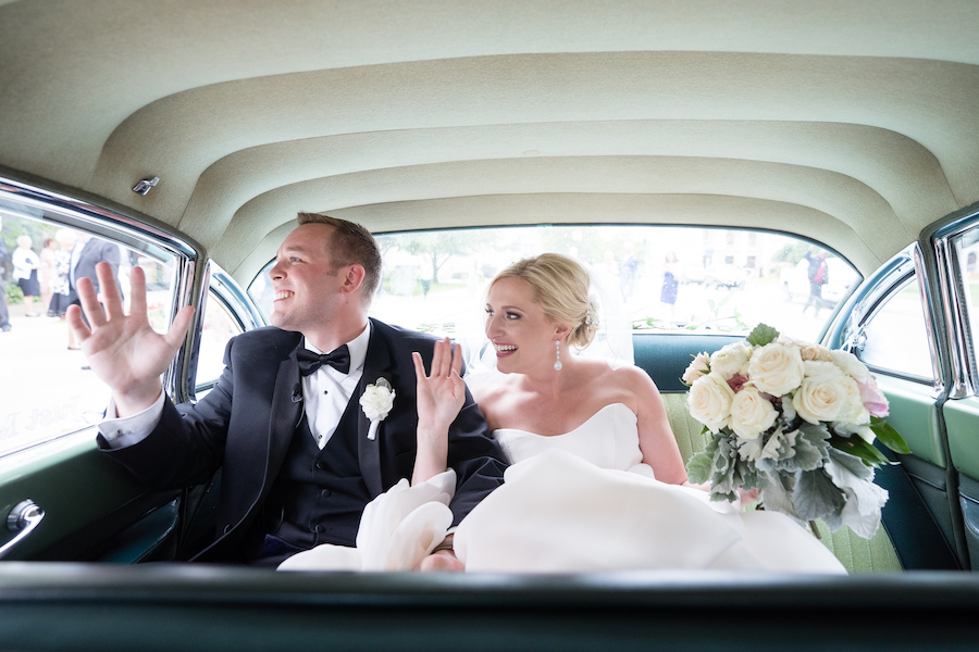 A bride and groom driving away during their Kalamazoo, Michigan wedding