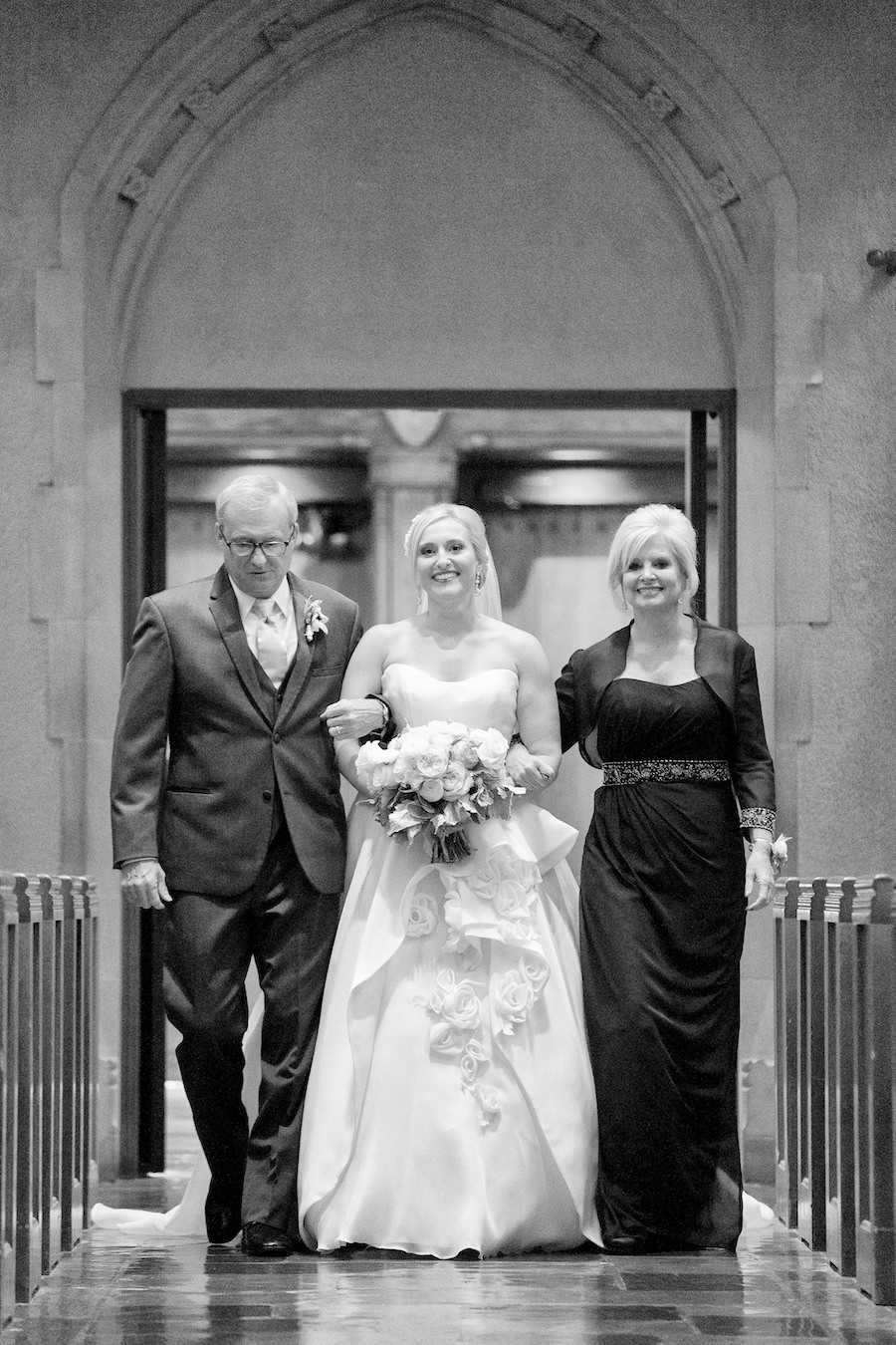 A bride walking down the aisle with her parents during her Kalamazoo, Michigan wedding