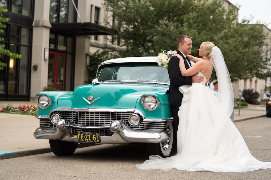 A bride and groom in front of a vintage car during their Kalamazoo, Michigan wedding