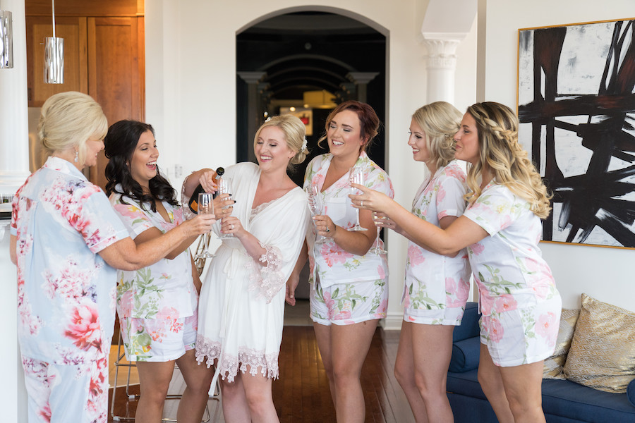 A bride and her bridesmaids sharing champagne the morning of her wedding