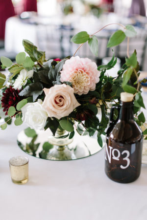 A blush and burgundy floral arrangement with a growler table number at a Loft 310 wedding
