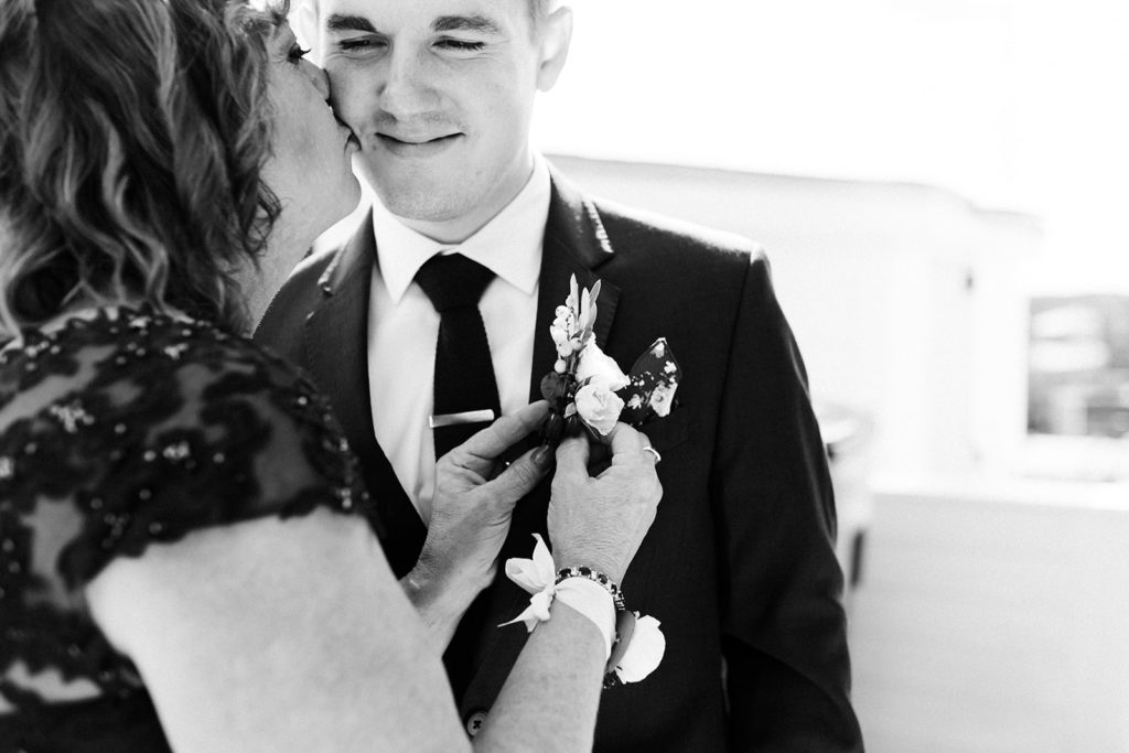 A mother putting a boutonnière on her son before his Loft 310 wedding