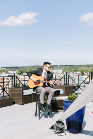 A musician playing guitar before a Sky Deck wedding in Kalamazoo, Michigan