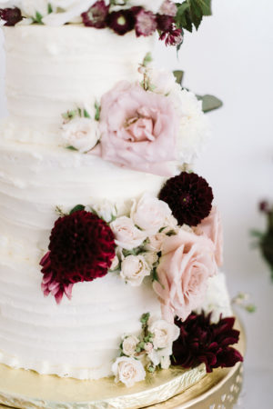 A white wedding cake with blush and burgundy flowers