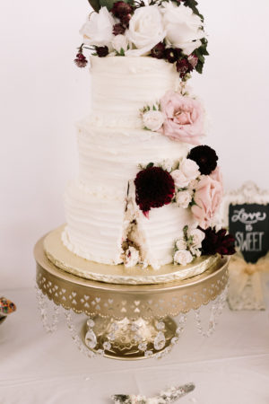 A white wedding cake with blush and burgundy flowers at a Loft 310 wedding