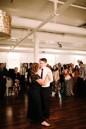 A mother and a groom share a dance during a loft 310 wedding