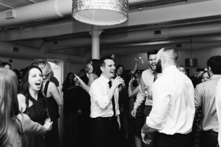 A groom laughing on the dance floor during his Kalamazoo, Michigan wedding