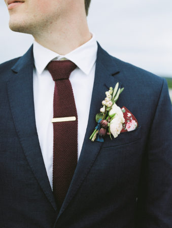A groom with a navy suit and burgundy tie