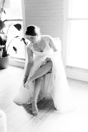 A bride putting on her wedding shoes before her Loft 310 wedding
