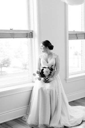 A bride looking out the window before her Kalamazoo, Michigan wedding