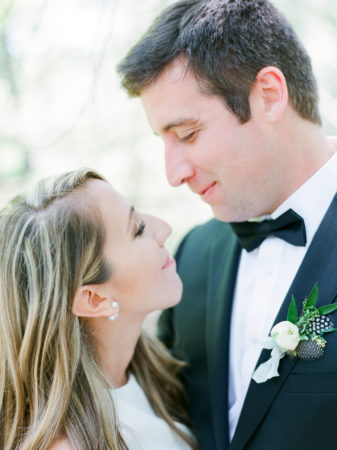 A bride and a groom smiling at each other before their Glen Arbor, Michigan wedding