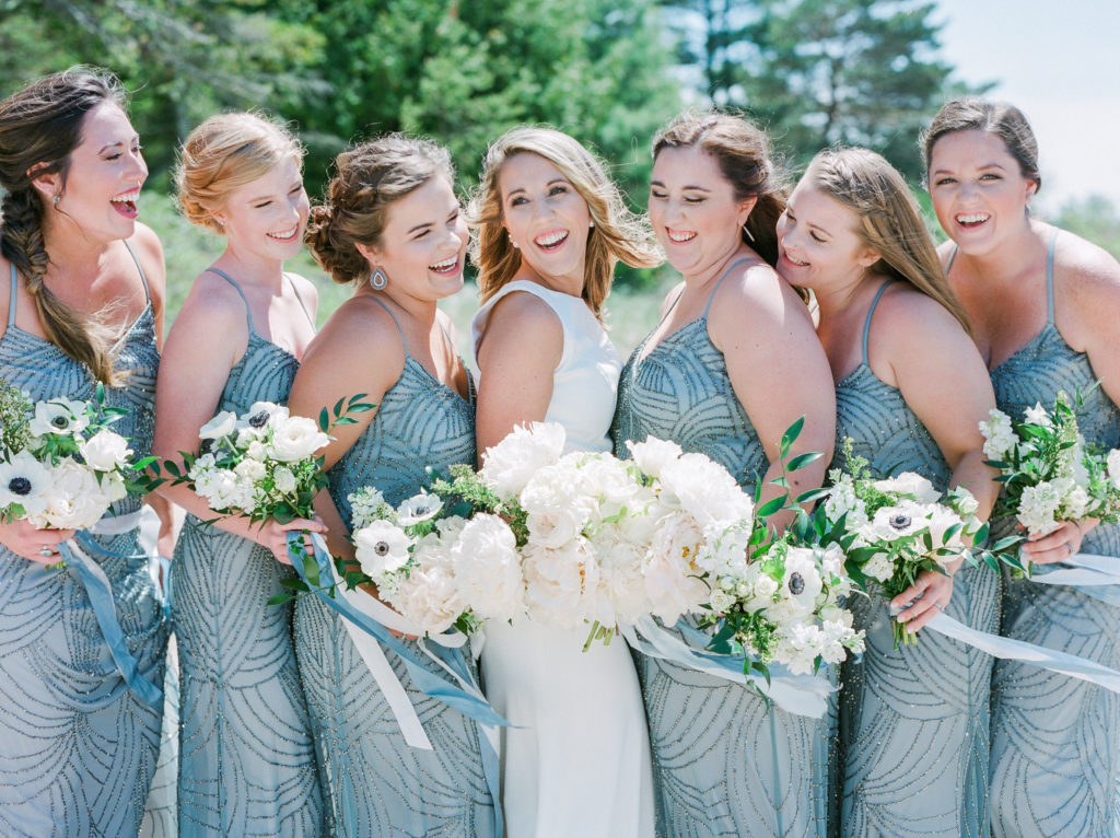 Bride and bridesmaids smiling before a Lake Michigan beach ceremony