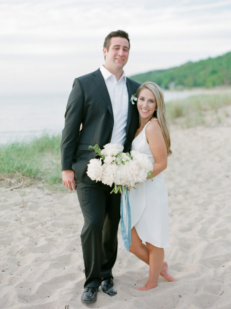 Bride and groom smiling on the beach after their Lake Michigan beach ceremony