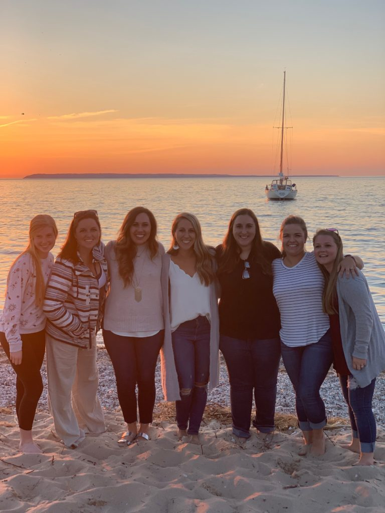 A group of ladies smiling during a sunset on Lake Michigan