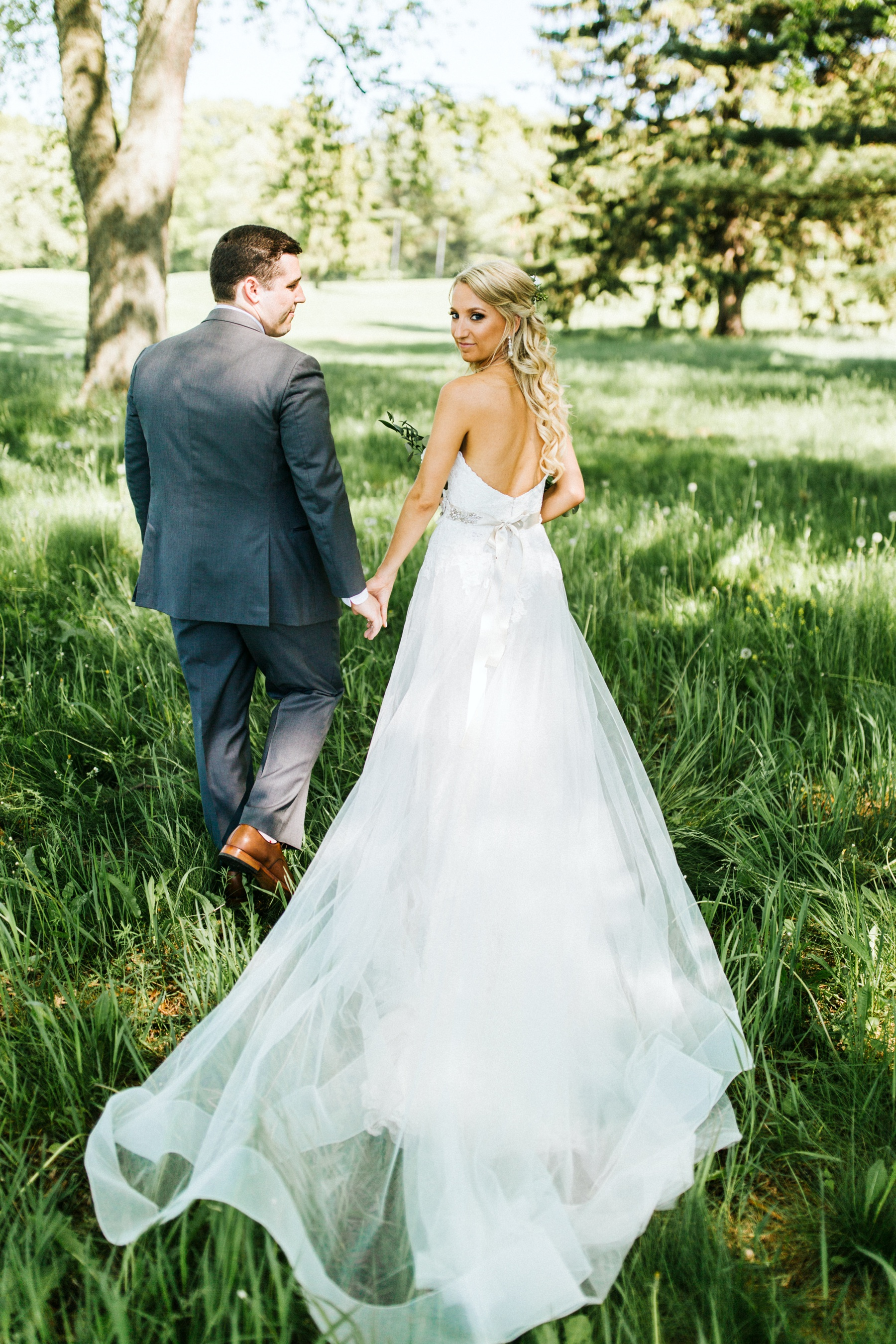 A bride and a groom walking outside before their spring lake country club wedding