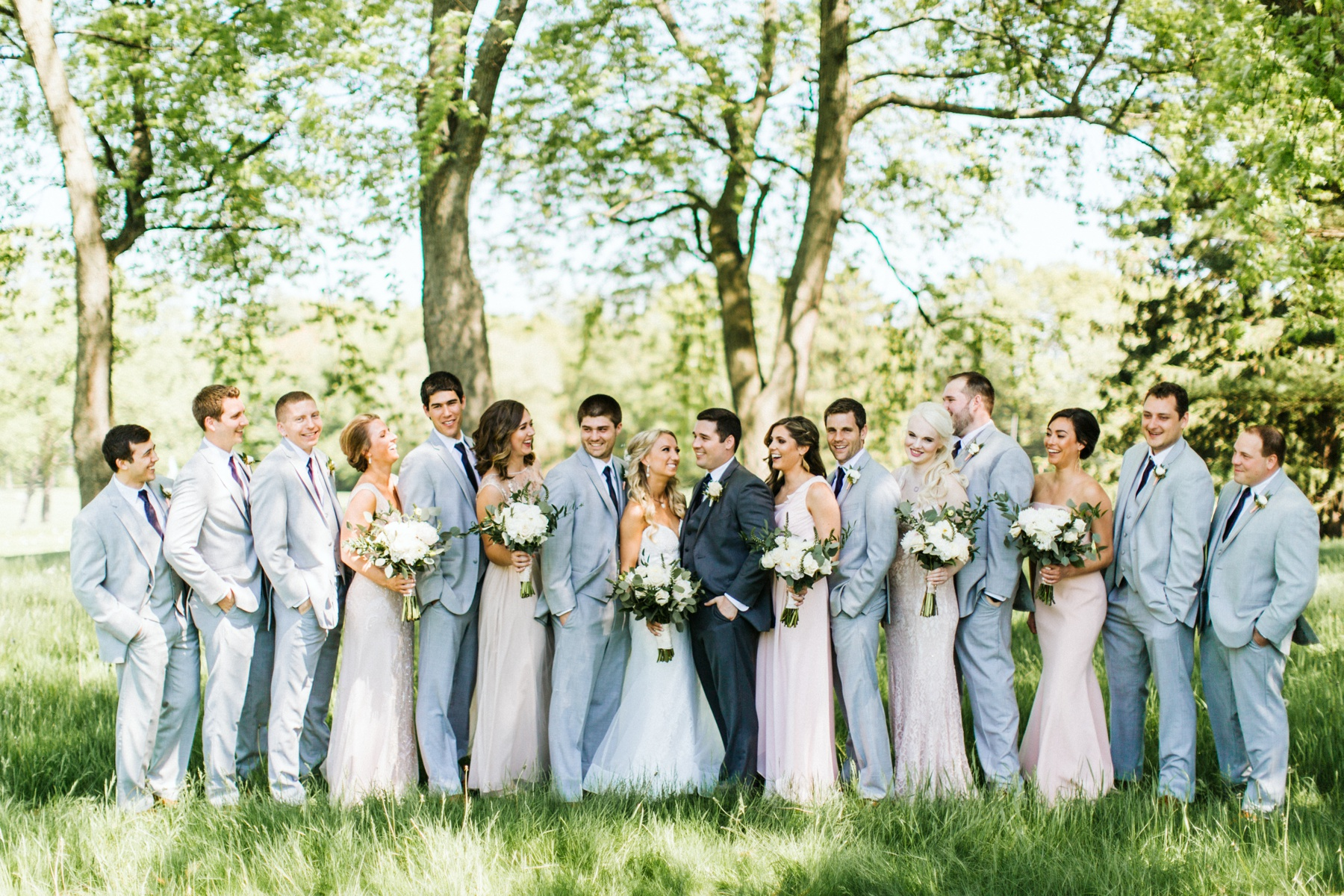 A wedding party smiling before a spring lake country club wedding