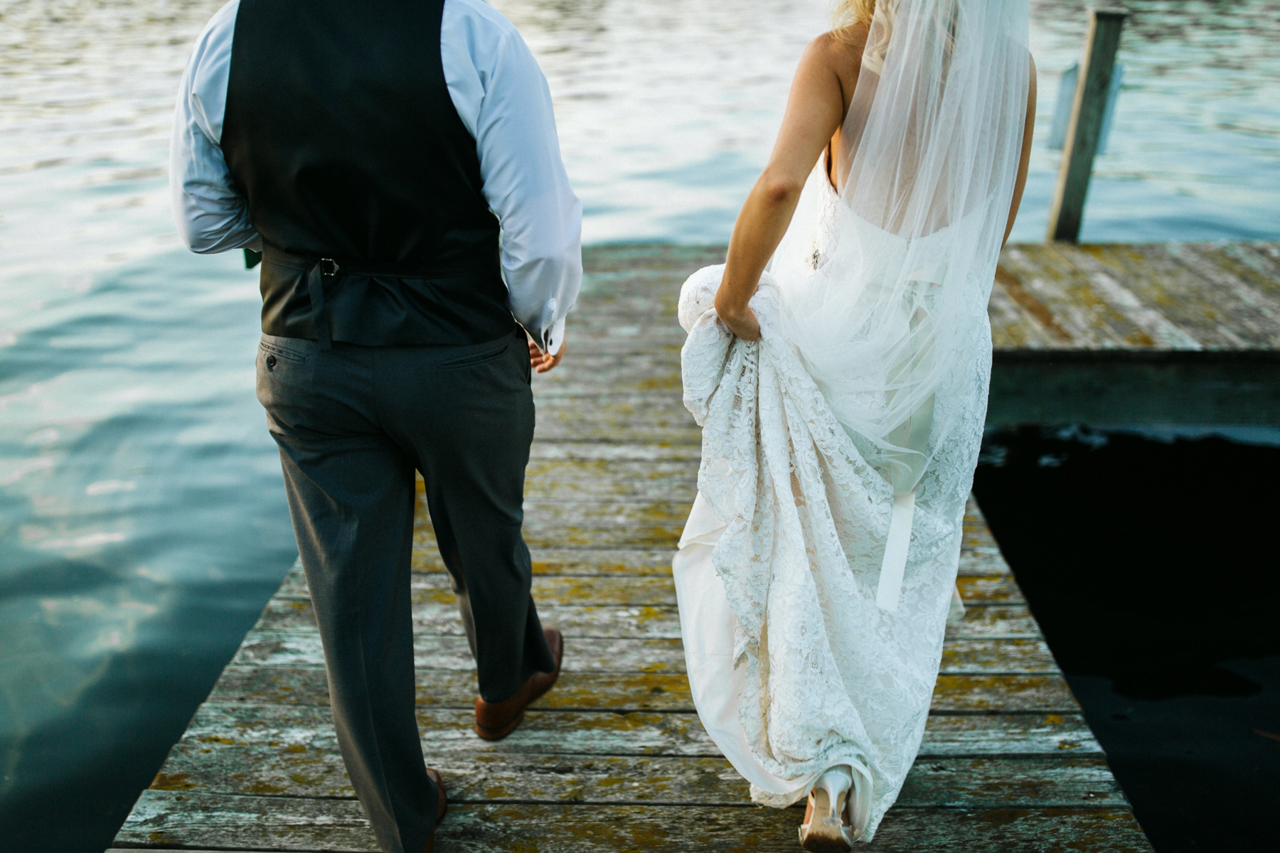 A bride and a groom walking by Spring lake during their spring lake country club wedding