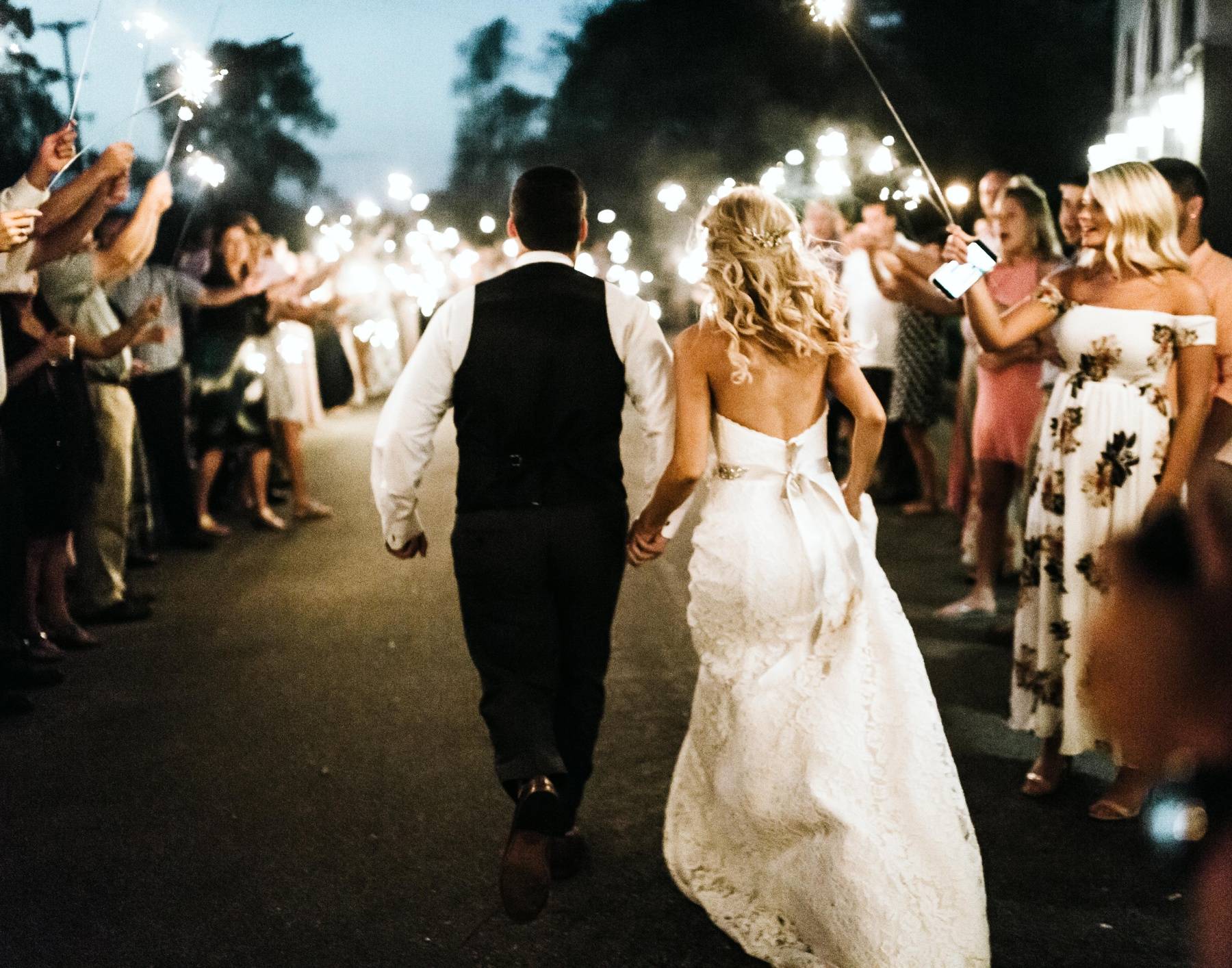 A couple walking through sparklers during their spring lake country club wedding