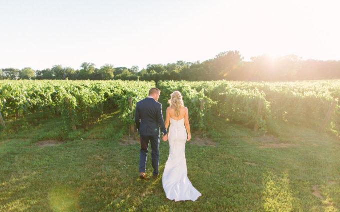 couple walking through a vineyard wedding in michigan