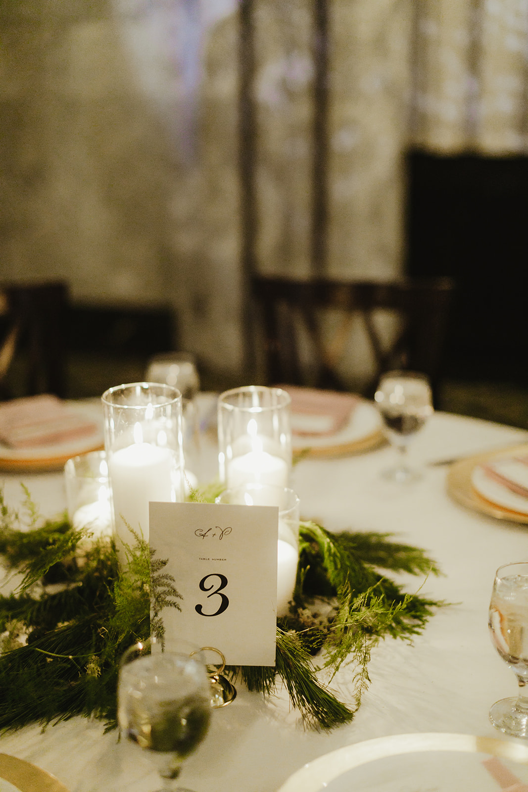 Candles and greenery on a table as wedding decor