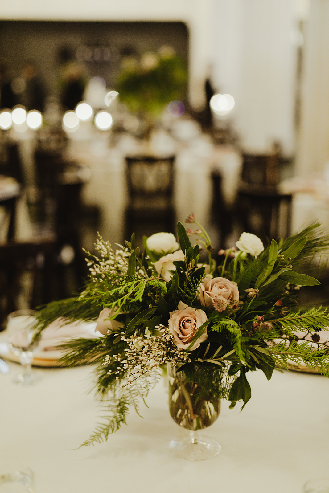 A blush and green floral arrangement on a table at a wedding