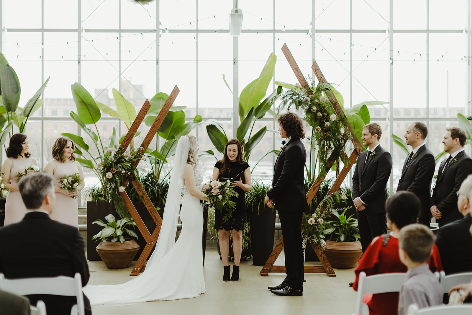 A couple and wedding party enjoying a ceremony during a Downtown Market Grand Rapids wedding