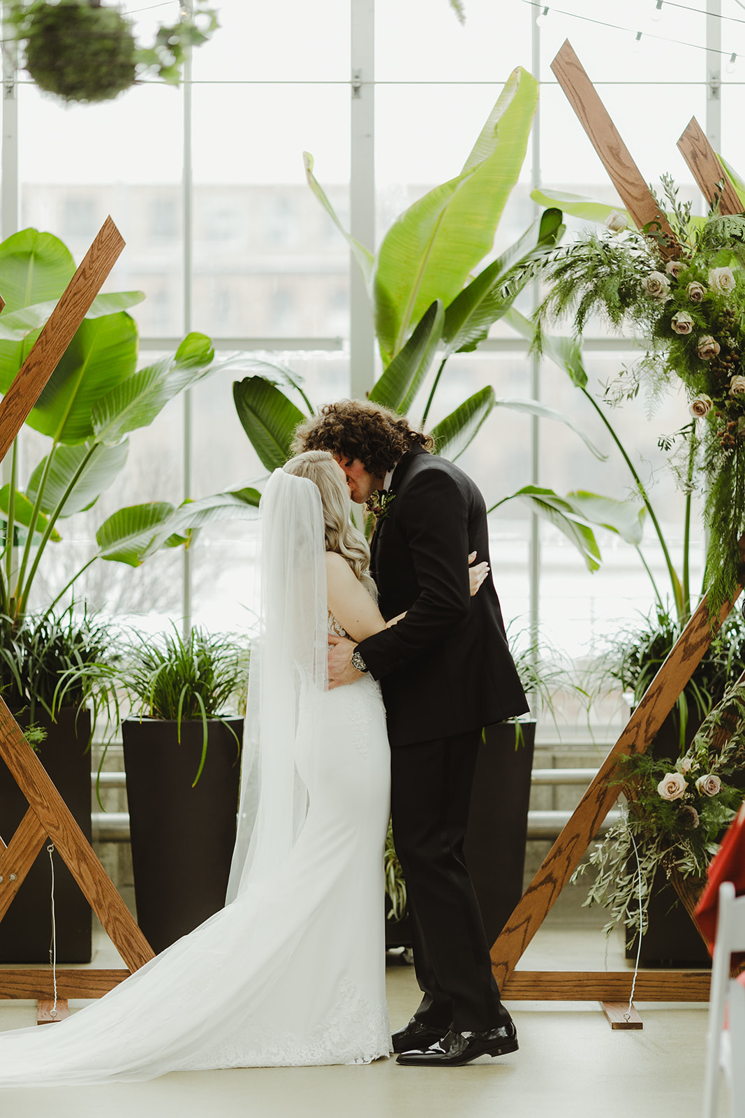 A couple sharing their first kiss during their Downtown Market Grand Rapids wedding