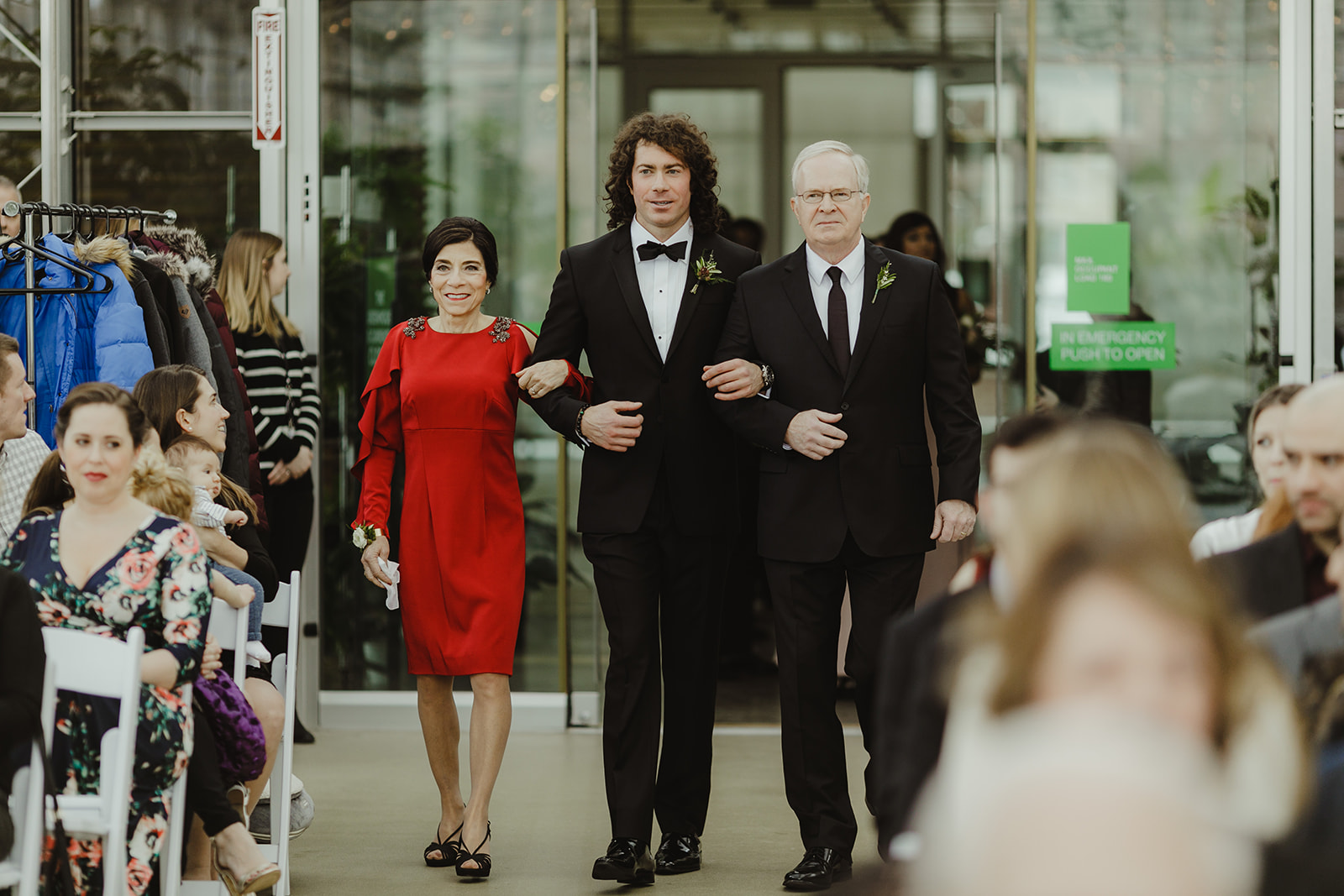 A groom walking his parents down the aisle