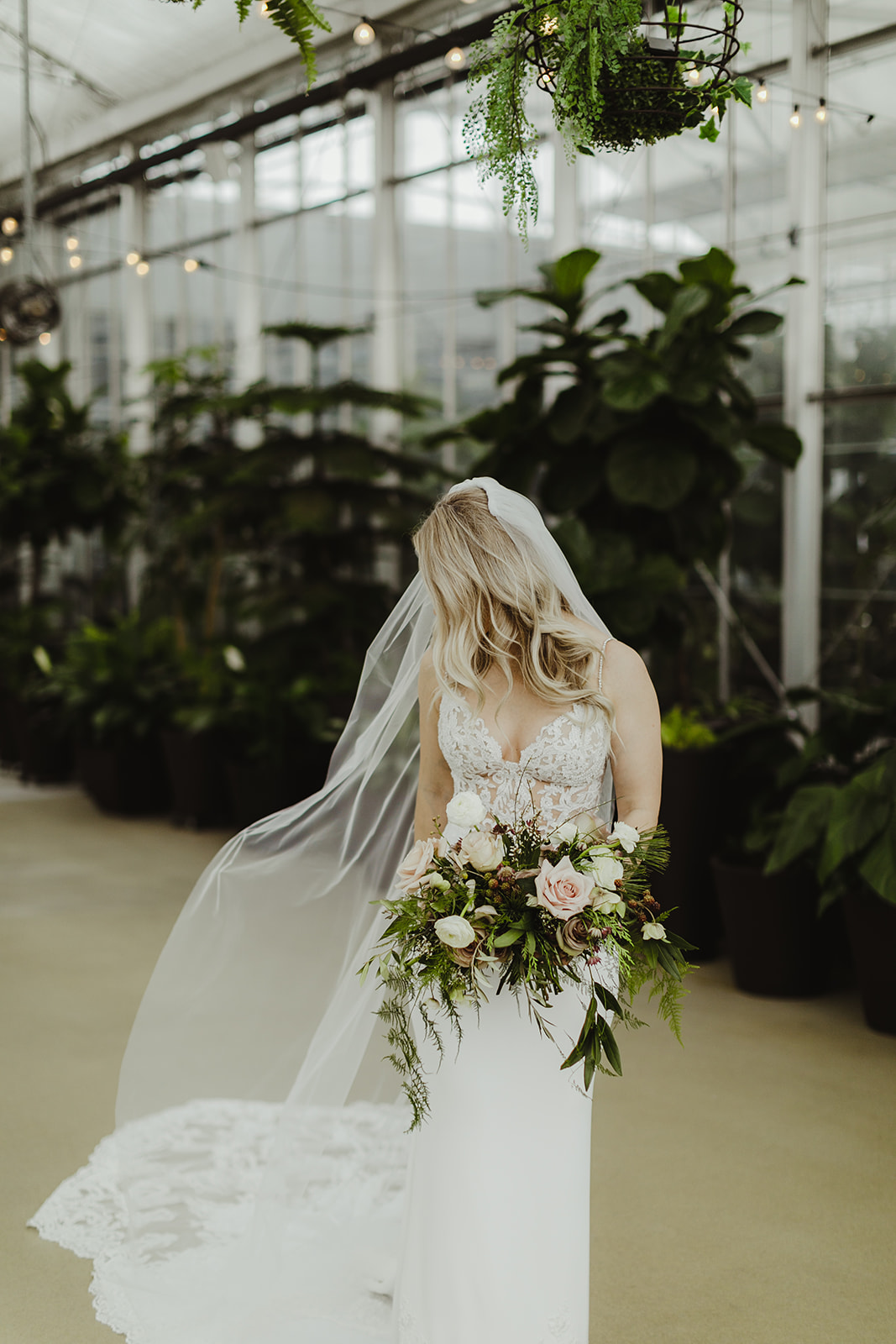 A bride smiling with her bouquet after her wedding ceremony