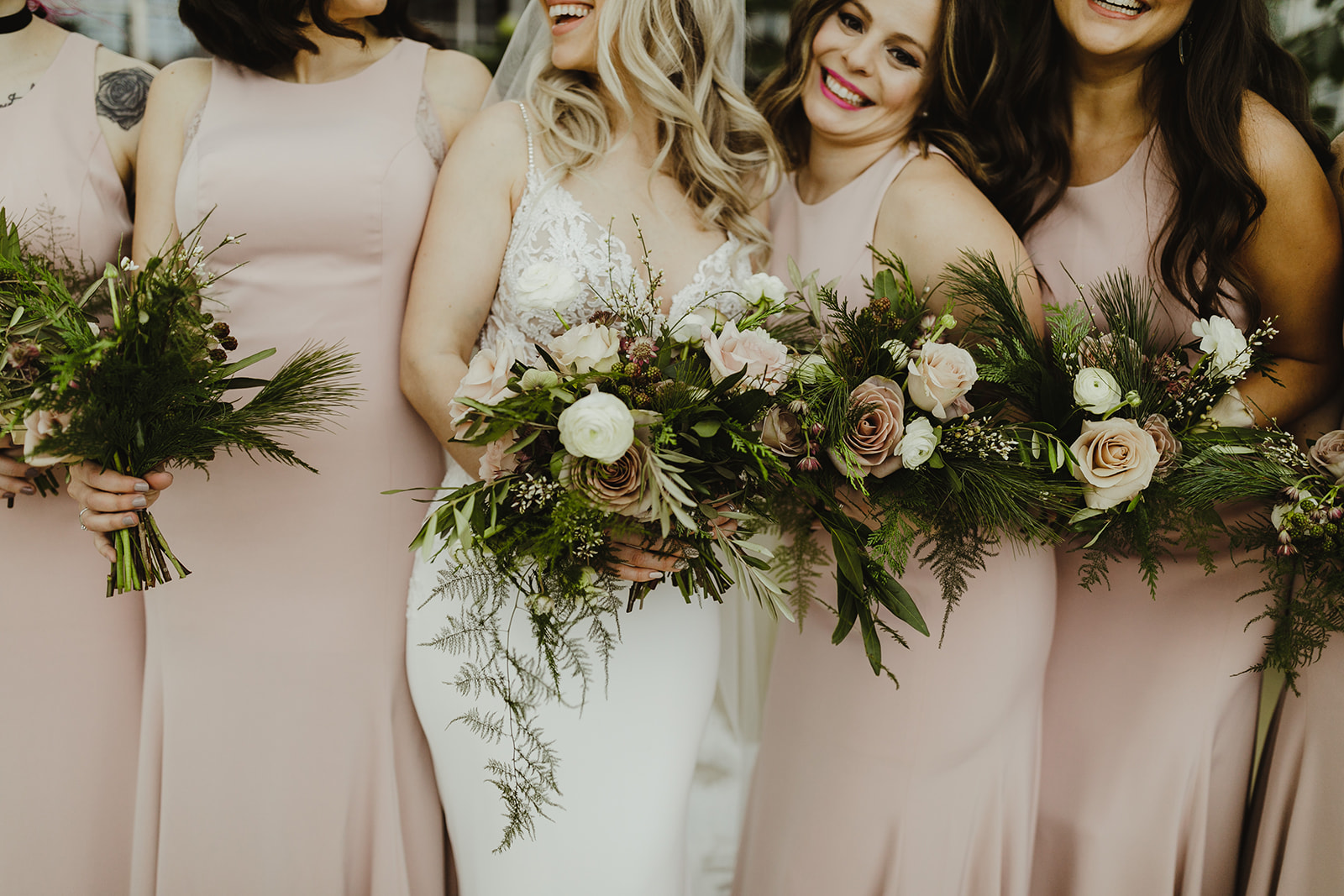 A bride and her bridesmaids smiling with their bouquets