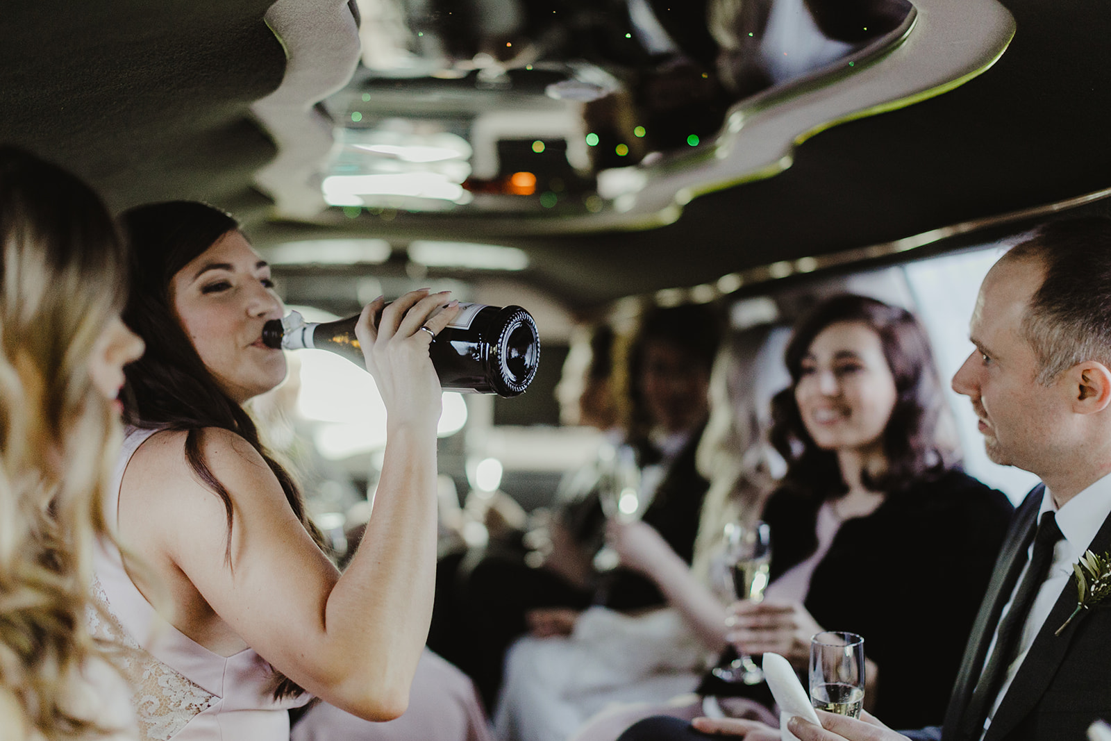A wedding part celebrating in a limo after a wedding ceremony