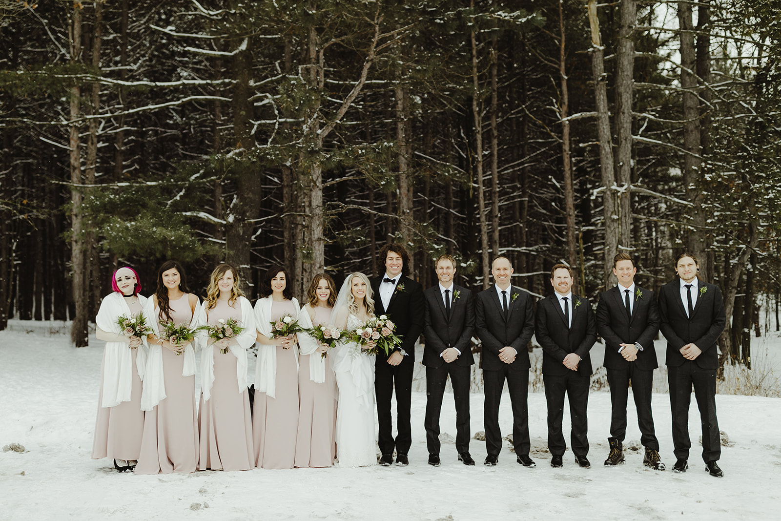 A wedding party smiling outside on a snowy Grand Rapids, Michigan day