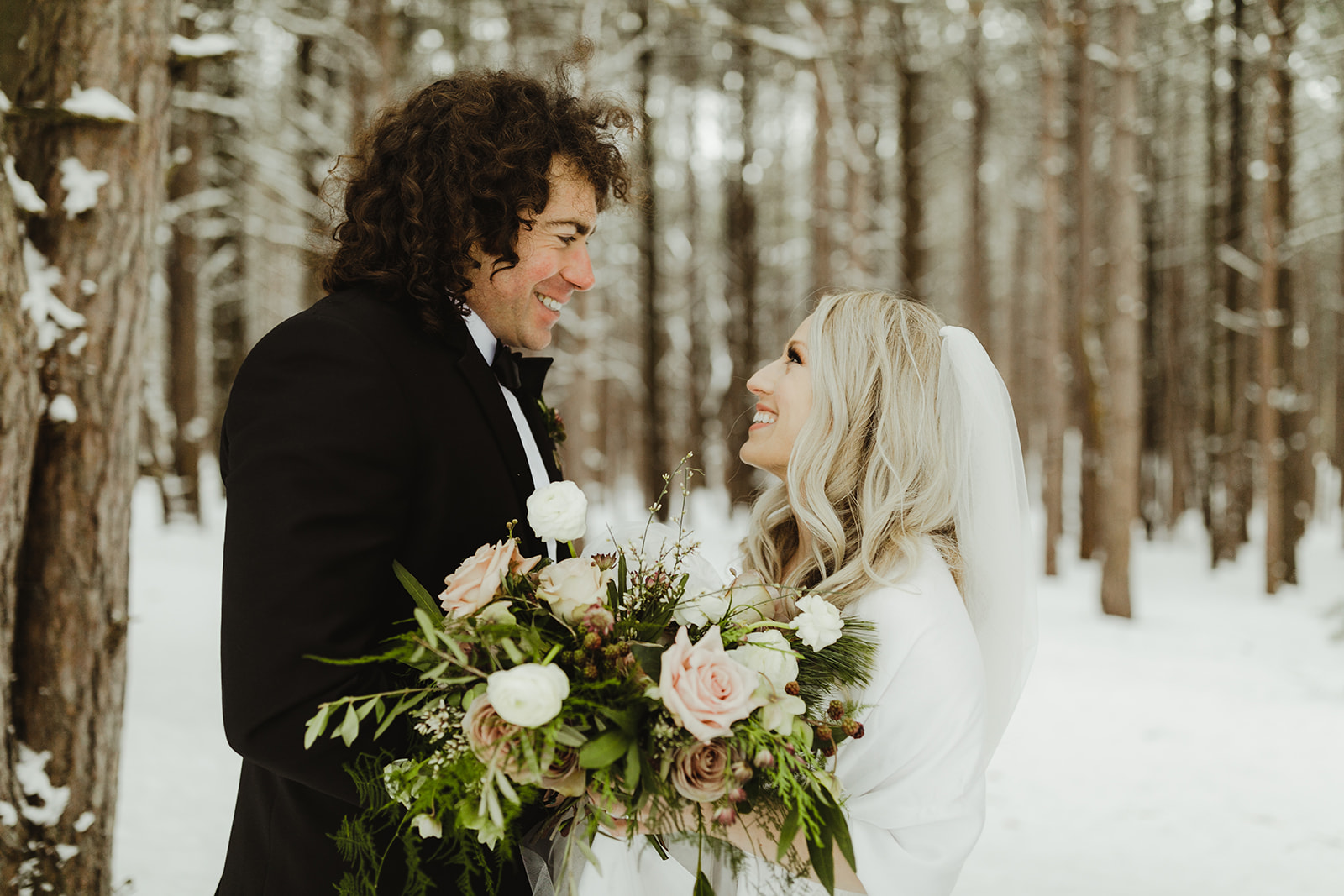 A bride and groom smiling in the snow after their Grand Rapids, Michigan wedding
