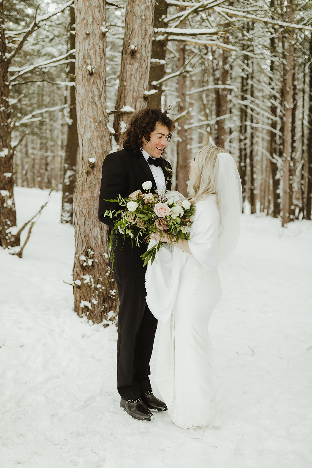 A bride and groom smiling in the snowy woods after their wedding