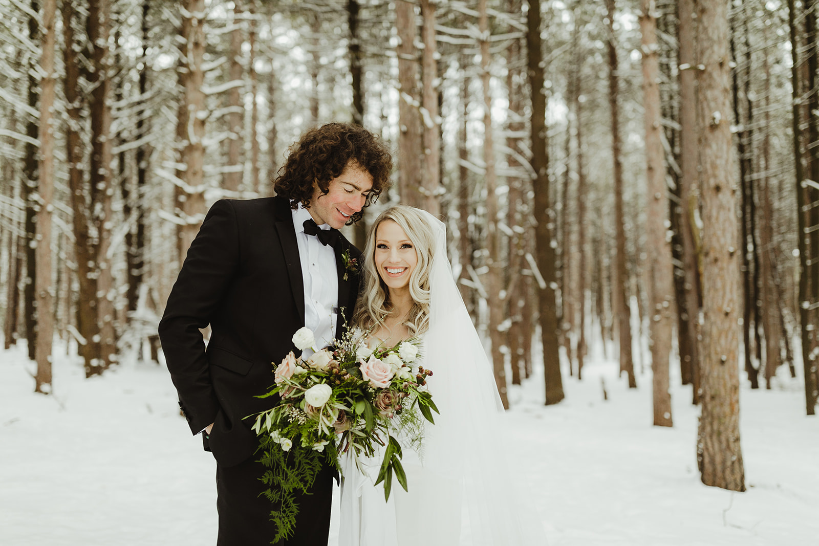 A bride smiling in the snowy woods after her Grand Rapids, Michigan wedding