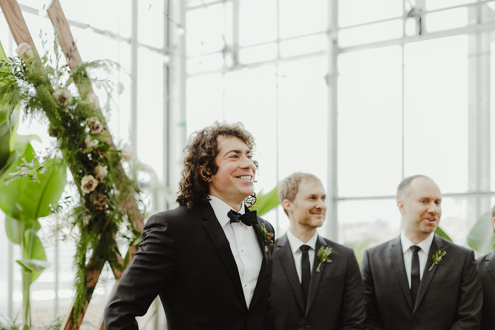 A groom smiling as his bride walks down the aisle