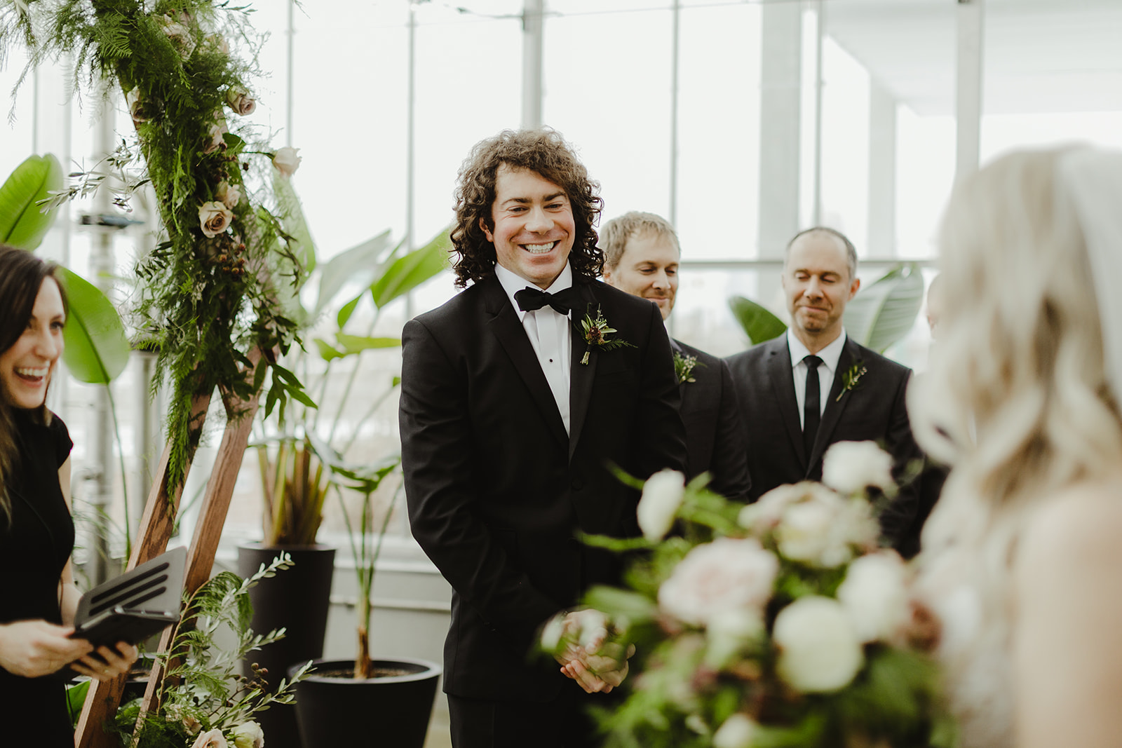 A groom smiling at his bride and she walks down the aisle