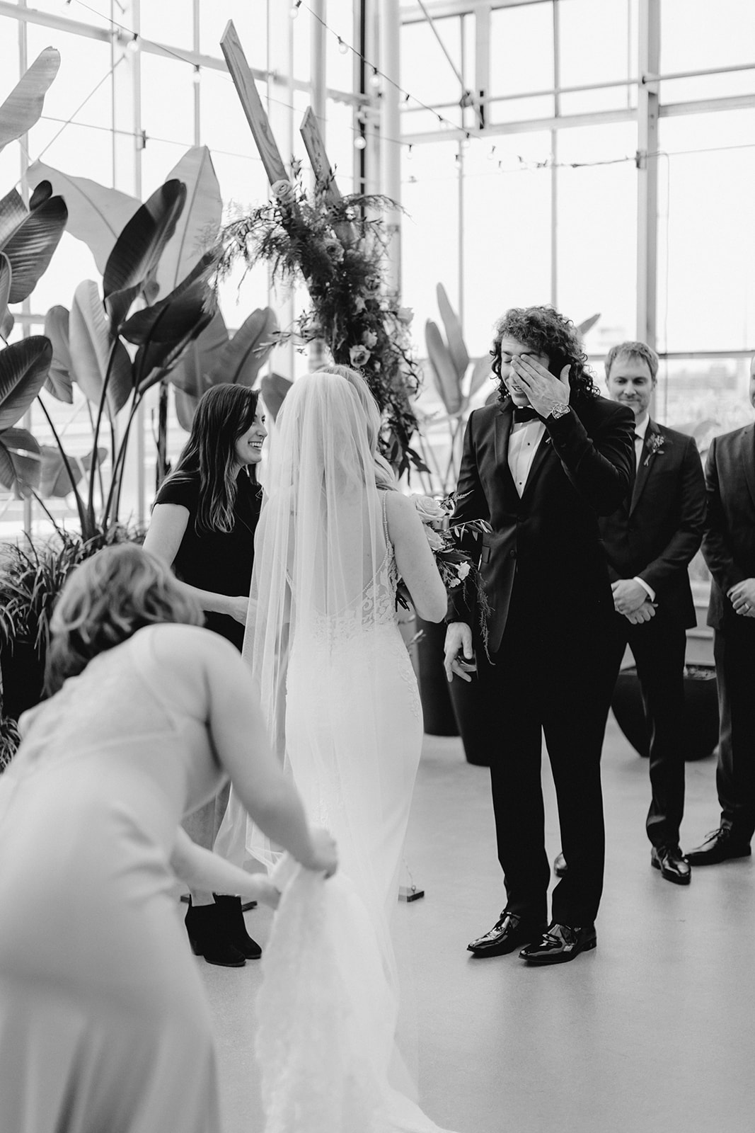 A groom crying as he reads his vows