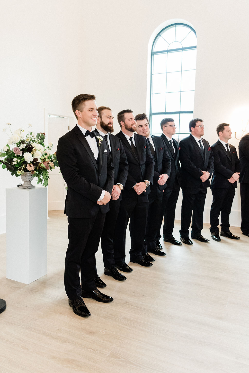 Groom and groomsmen smiling during a wedding